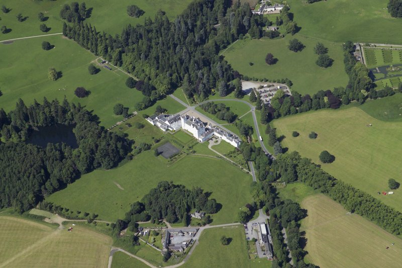 General oblique aerial view centred on the country house, bridge and gardens with the dairy, offices and church adjacent, taken from the S.
