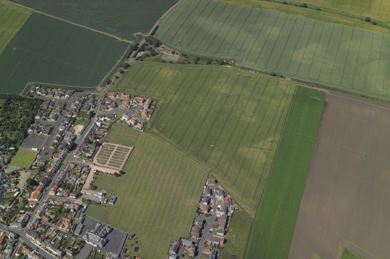 Oblique aerial view centred on the cropmarks of the rig and possible bell pits with the railway station and school adjacent, taken from the SW.