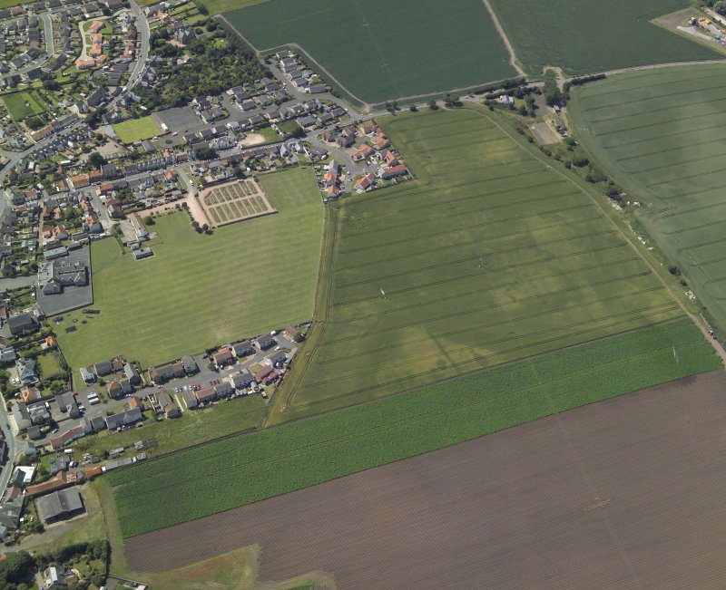 Oblique aerial view centred on the cropmarks of the rig and possible bell pits with the railway station and school adjacent, taken from the ENE.