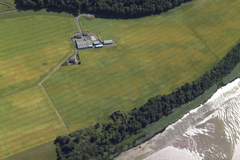 Oblique aerial view centred on the cropmarks of the enclosures and field boundaries with the farmhouse, farmsteading and remains of the castle adjacent, taken from the N.
