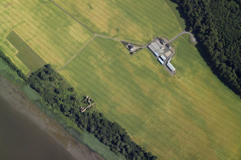 Oblique aerial view centred on the cropmarks of the enclosures and field boundaries with the farmhouse, farmsteading and remains of the castle adjacent, taken from the NW.
