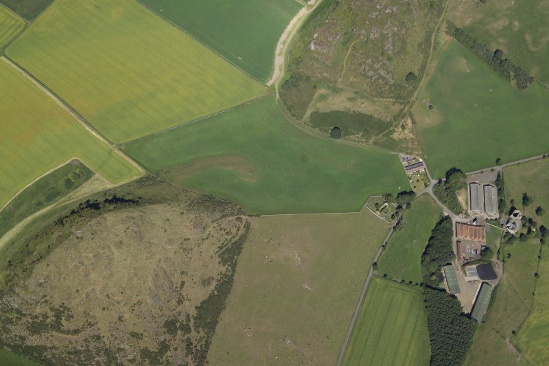 Oblique aerial view centred on the parchmarks of the enclosure with the farmsteading, tower-house and remains of the church and fort adjacent, taken from the SW.