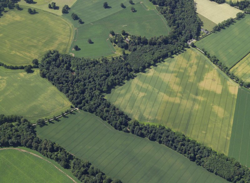 General oblique aerial view centred on the cropmarks of the ring-ditch and barrows with the church, burial-ground and remains of the stone adjacent, taken from the ESE.