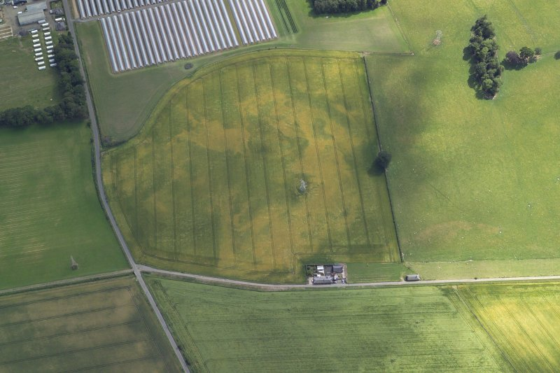 Oblique aerial view centred on the cropmarks of the pits, curvilinear enclosure, ring-ditch and possible unenclosed settlement, taken from the N.