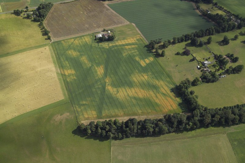 Oblique aerial view centred on the cropmarks of the Roman fortress and ring-ditch with the country house, farmhouse and farmsteading adjacent, taken form the NNW.