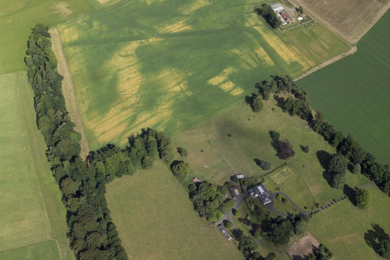 Oblique aerial view centred on the cropmarks of the Roman fortress and ring-ditch with the country house, farmhouse and farmsteading adjacent, taken form the W.