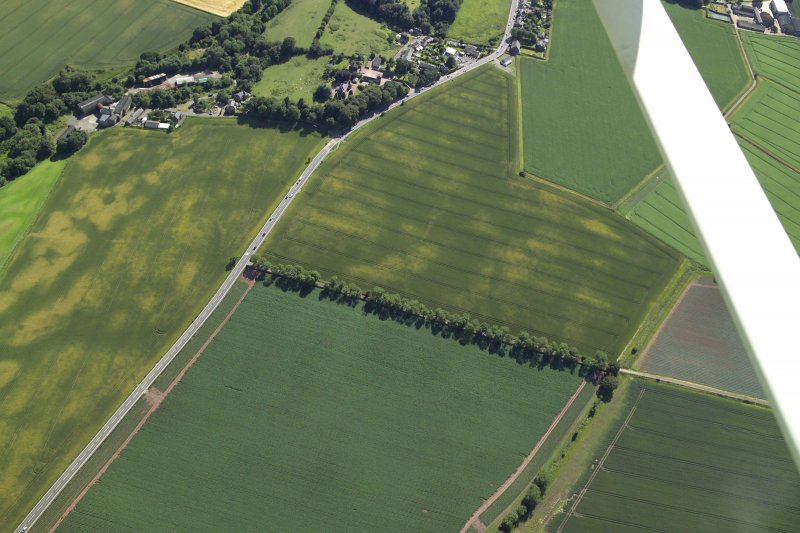 Oblique aerial view centred on the cropmarks of the barrows with the church adjacent, taken from the NE.