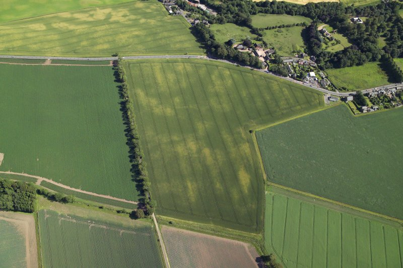 Oblique aerial view centred on the cropmarks of the barrows with the church adjacent, taken from the NNW.