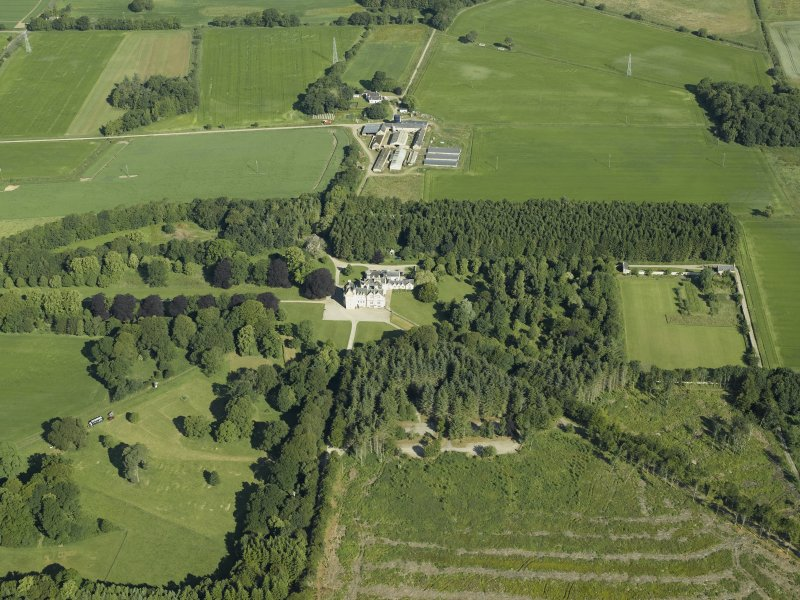 Oblique aerial view centred on the castle, country house and walled garden with the sawmill adjacent, taken from the SE.
