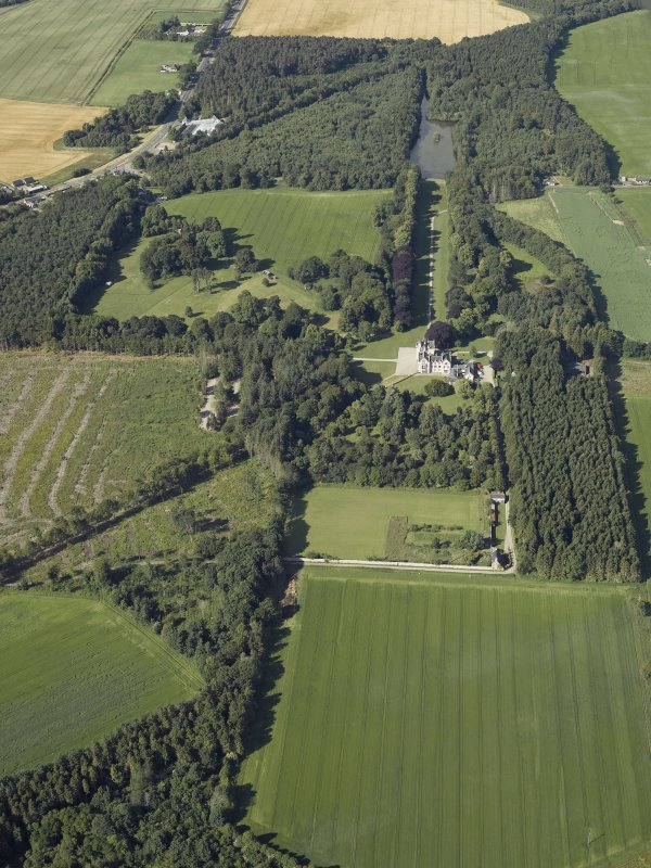 Oblique aerial view centred on the castle, country house and walled garden with the lodge adjacent, taken from the NE.