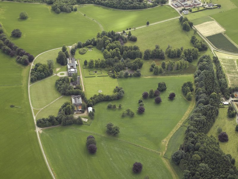 Oblique aerial view centred on the country house, tower-house, farmhouse, farmsteading, cottages and stables, taken from the W.
