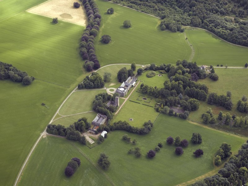 Oblique aerial view centred on the country house, tower-house, farmhouse, farmsteading, cottages and stables, taken from the WSW.
