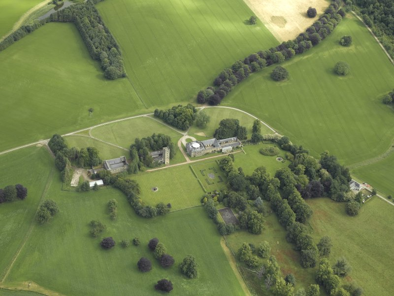 Oblique aerial view centred on the country house, tower-house, farmhouse, farmsteading, cottages and stables, taken from the S.