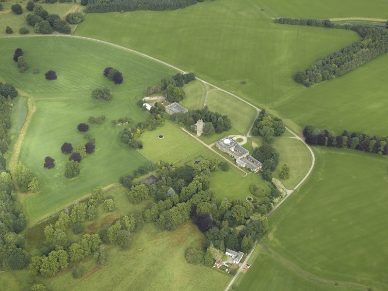 Oblique aerial view centred on the country house, tower-house, farmhouse, farmsteading, cottages and stables, taken from the ESE.