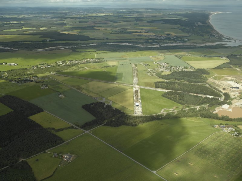 General oblique aerial view centred on the airfield with the villages in the distance, taken from the E.