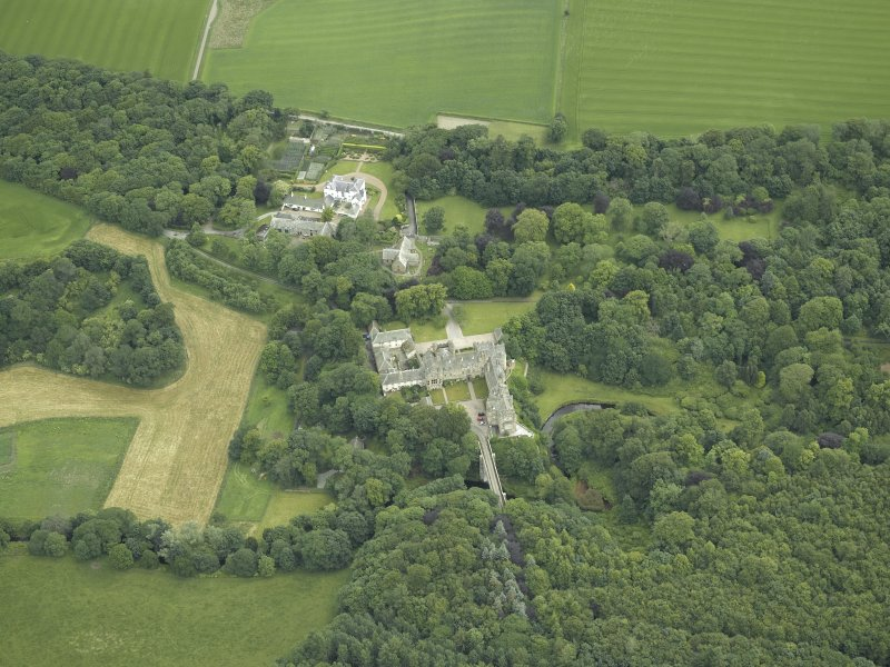 Oblique aerial view centred on the country house, stables and bridge, taken from the WSW.