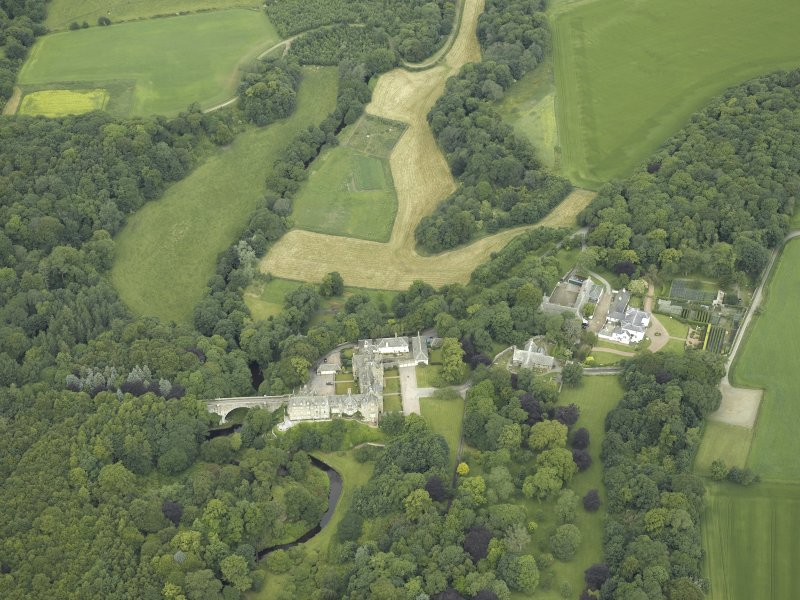 Oblique aerial view centred on the country house, stables and bridge, taken from the SW.