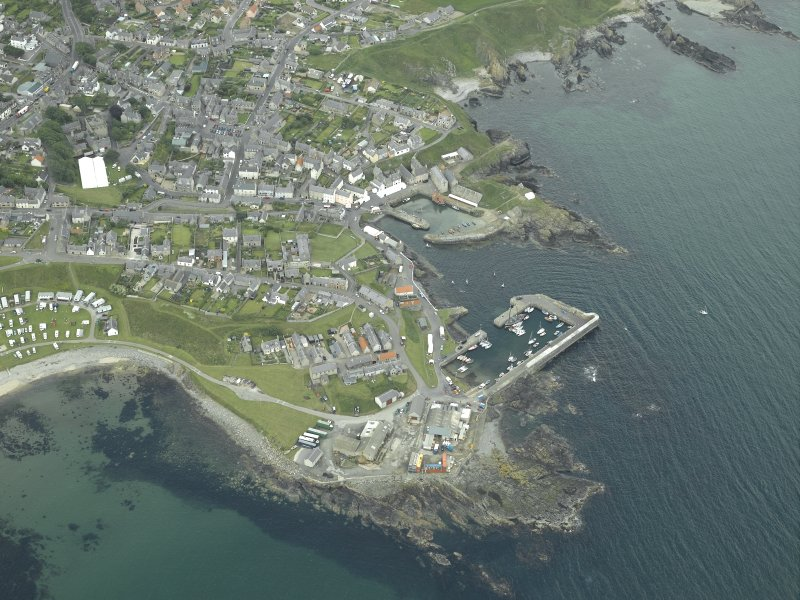Oblique aerial view of the village centred on the harbours, taken from the NE.