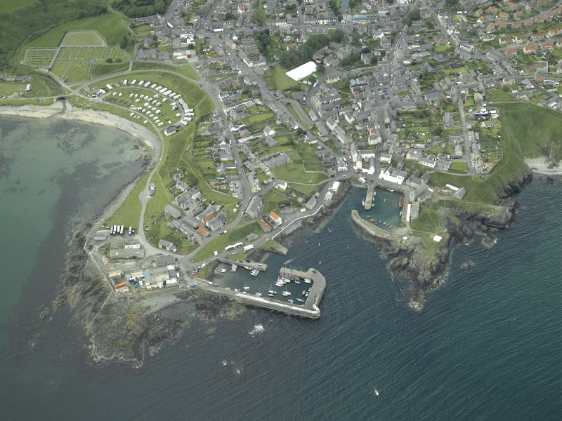 Oblique aerial view of the village centred on the harbours, taken from the N.