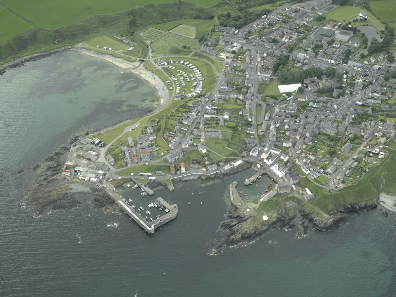 Oblique aerial view of the village centred on the harbours, taken from the NW.