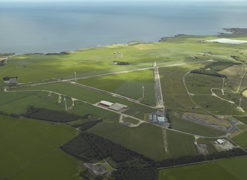 General oblique aerial view centred on the remains of the airfield and the wind farm, taken from the SW.