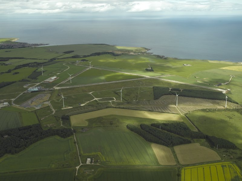 General oblique aerial view centred on the remains of the airfield and the wind farm, taken from the SE.