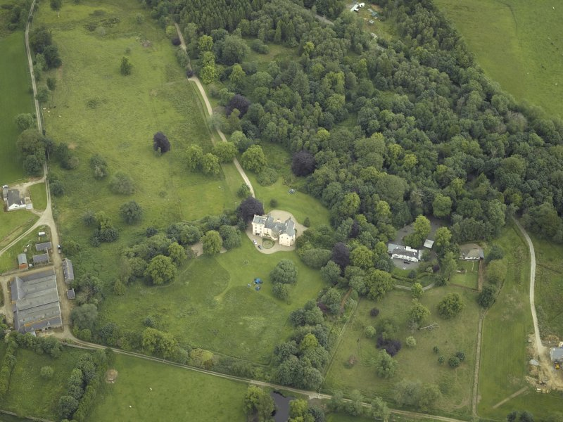 Oblique aerial view centred on the country house with the farmhouse and farmsteading adjacent, taken from the SSW.