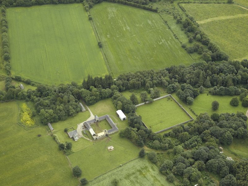 Oblique aerial view centred on the farmhouse, farmsteading and walled garden, taken from the NW.