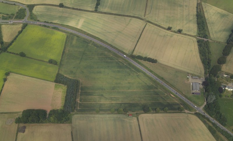 Oblique aerial view centred on the cropmarks of the Roman temporary camps and possible fort annexe, taken from the SSE.