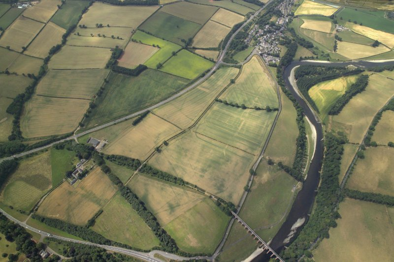 General oblique aerial view centred on the cropmarks of the Roman fort, Roman temporary camps and fort annexes with the railway viaduct adjacent and village in the distance, taken from the NE.