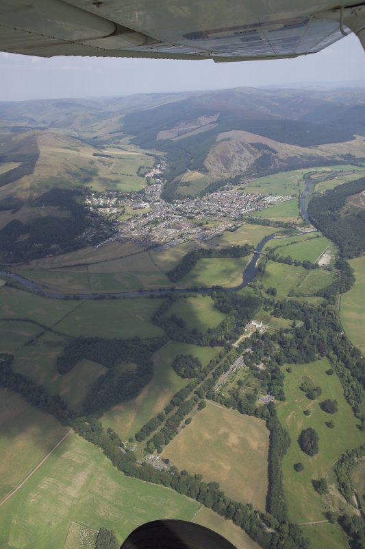 General oblique aerial view centred on the town with the country house in the foreground, taken from the SSW.
