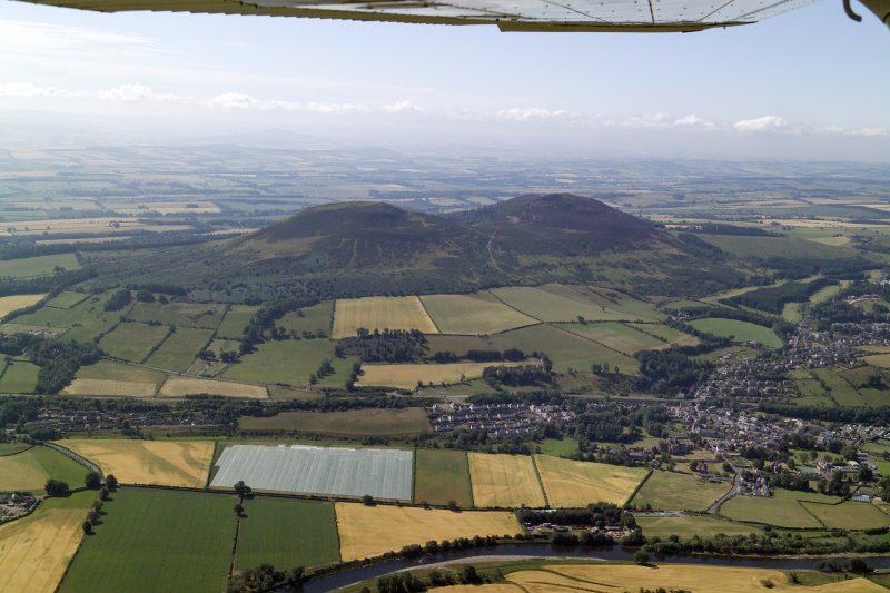 General oblique aerial view centred on the remains of the fort and the Eildon Hills with the town in the foreground, taken from the NNW.