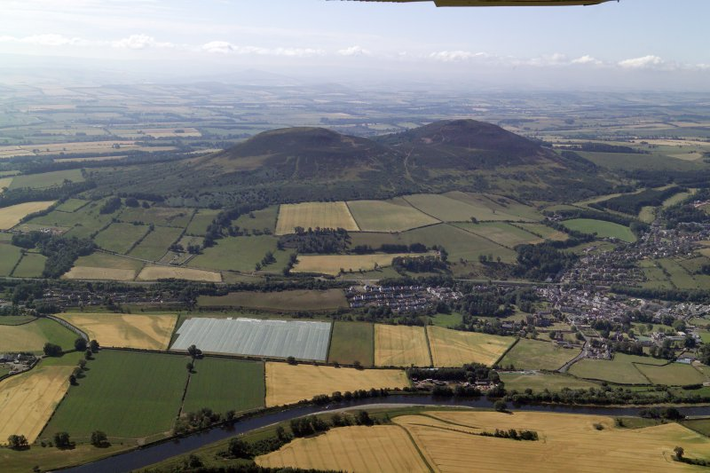 General oblique aerial view centred on the remains of the fort and the Eildon Hills with the town in the foreground, taken from the N.