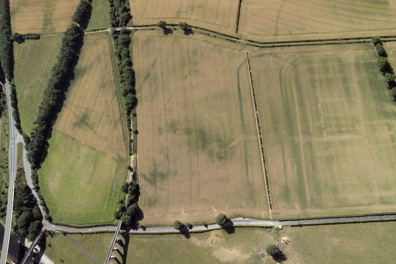 Oblique aerial view centred on the cropmarks of the Roman fort, Roman temporary camps and fort annexes, taken from the NNW.