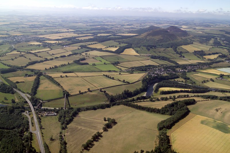 General oblique aerial view centred on the cropmarks of the Roman fort and Roman temporary camps with the town, village and remains of the fort in the distance and the railway viaduct and road bridge  ...