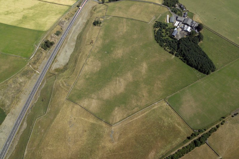 Oblique aerial view centred on the parchmarks and remains of the fort, taken from the SW.