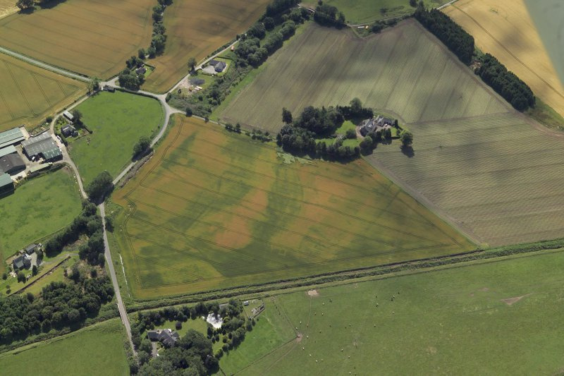 Oblique aerial view centred on the cropmarks of the enclosures and possible building with the manse and remains of the abbey adjacent, taken from the NE.