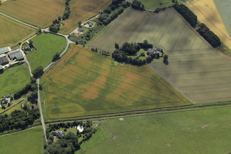 Oblique aerial view centred on the cropmarks of the enclosures and possible building with the manse and remains of the abbey adjacent, taken from the NNE.