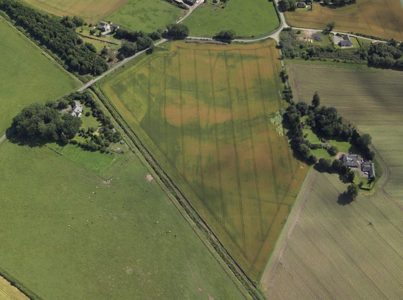 Oblique aerial view centred on the cropmarks of the enclosures and possible building with the manse and remains of the abbey adjacent, taken from the NW.