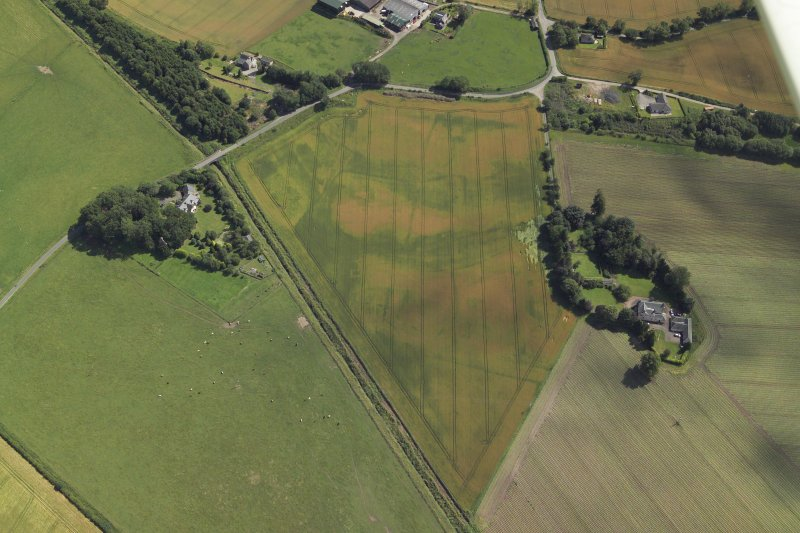 Oblique aerial view centred on the cropmarks of the enclosures and possible building with the manse and remains of the abbey adjacent, taken from the WNW.