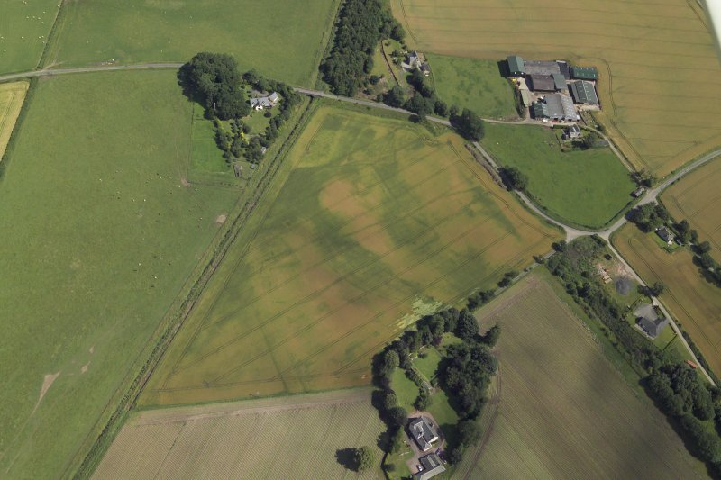Oblique aerial view centred on the cropmarks of the enclosures and possible building with the manse, farmsteading, farmhouse and remains of the abbey adjacent, taken from the W.