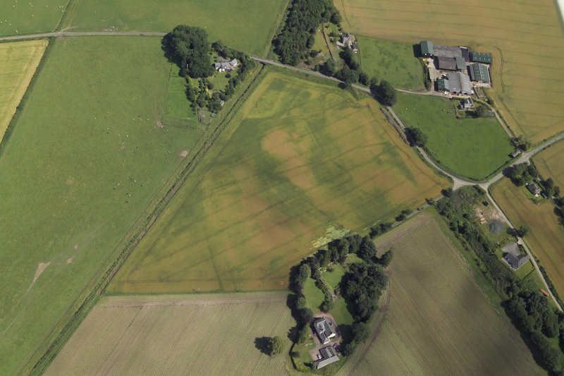 Oblique aerial view centred on the cropmarks of the enclosures and possible building with the manse, farmsteading, farmhouse and remains of the abbey adjacent, taken from the WSW.