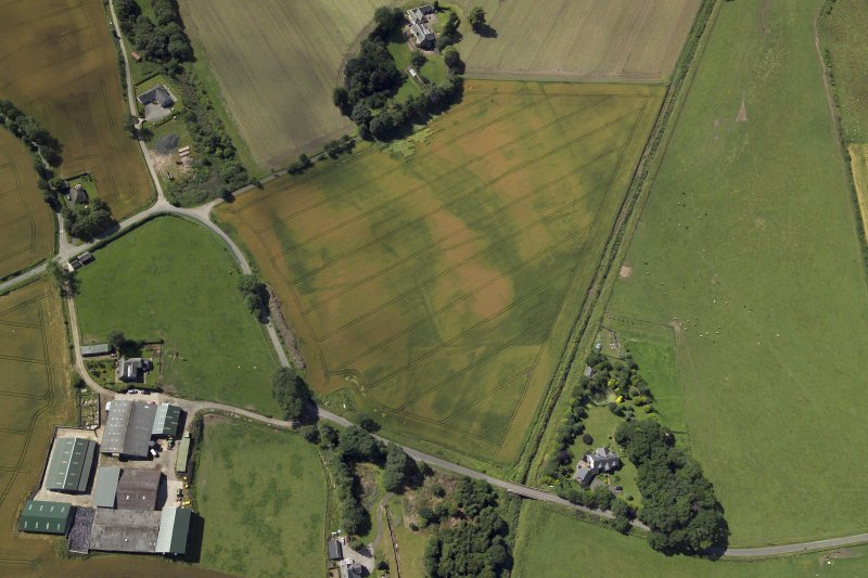 Oblique aerial view centred on the cropmarks of the enclosures and possible building with the manse, farmsteading, farmhouse and remains of the abbey adjacent, taken from the E.