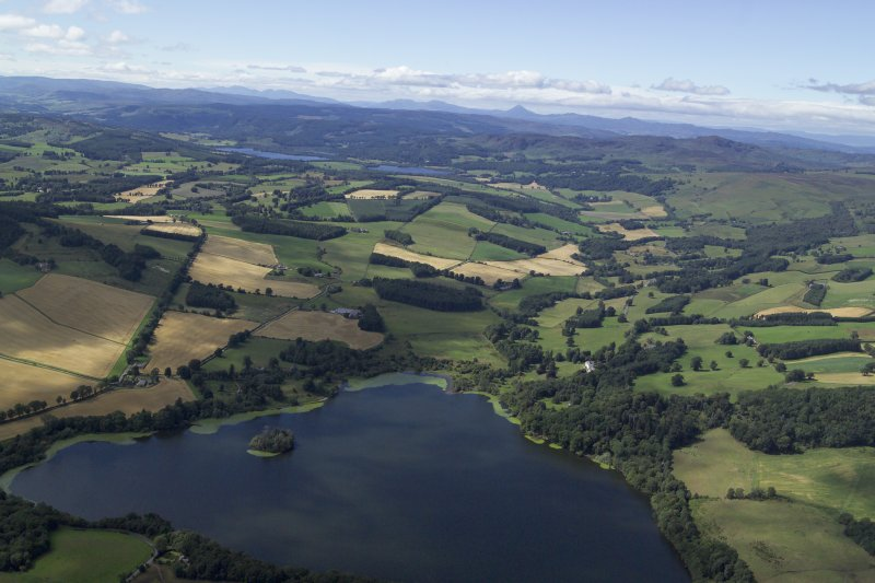 General oblique aerial view looking across the Loch of Clunie towards the Grampian Mountains with the remains of the possible crannog and the church and country house in the foreground, taken from the E.