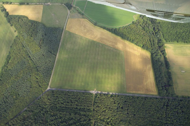 Oblique aerial view centred on the cropmarks of the settlement and ring-ditches, taken from the WSW.
