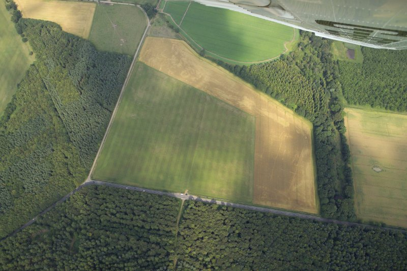 Oblique aerial view centred on the cropmarks of the settlement and ring-ditches, taken from the SW.