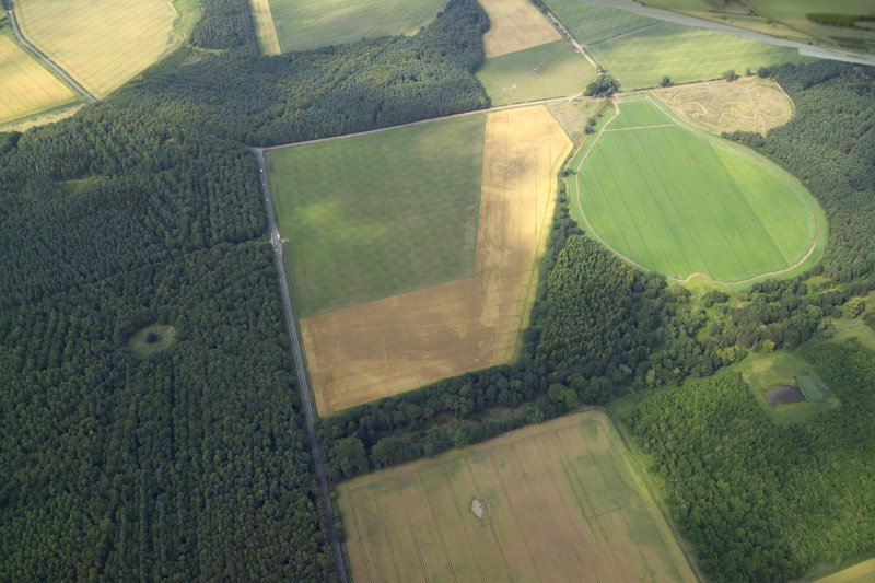 Oblique aerial view centred on the cropmarks of the settlement and ring-ditches, taken from the SSE.
