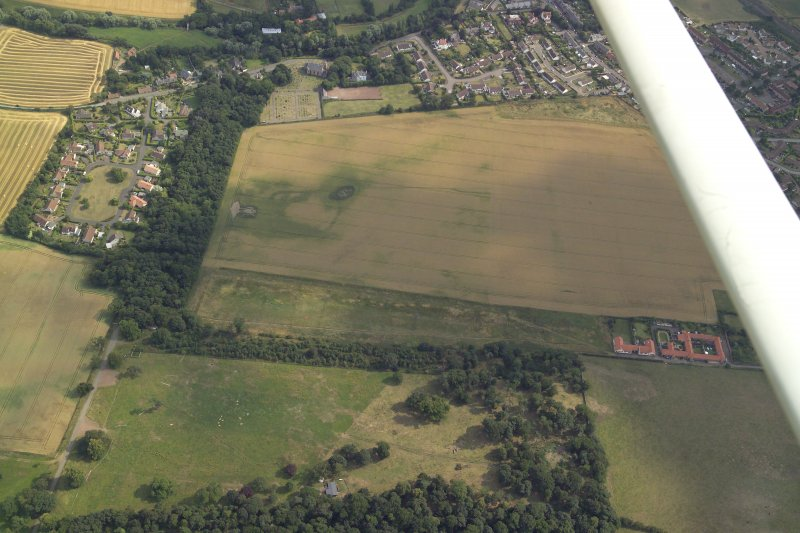General oblique aerial view centred on the cropmarks of the settlement with the church and burial-ground adjacent, taken from the NNW.