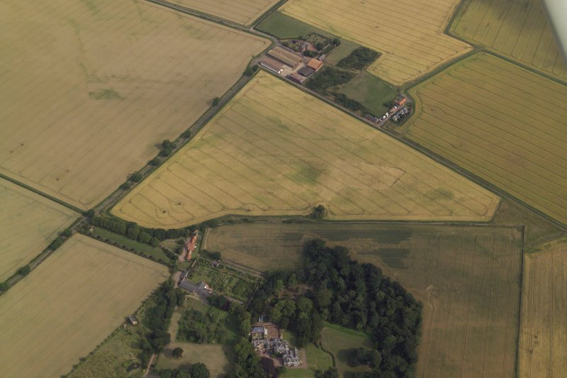 Oblique aerial view centred on the cropmarks of the field boundary and the cropmarks of the quarry with the farmhouse, farmsteading, country house, walled garden and dovecot adjacent, taken from the NW.