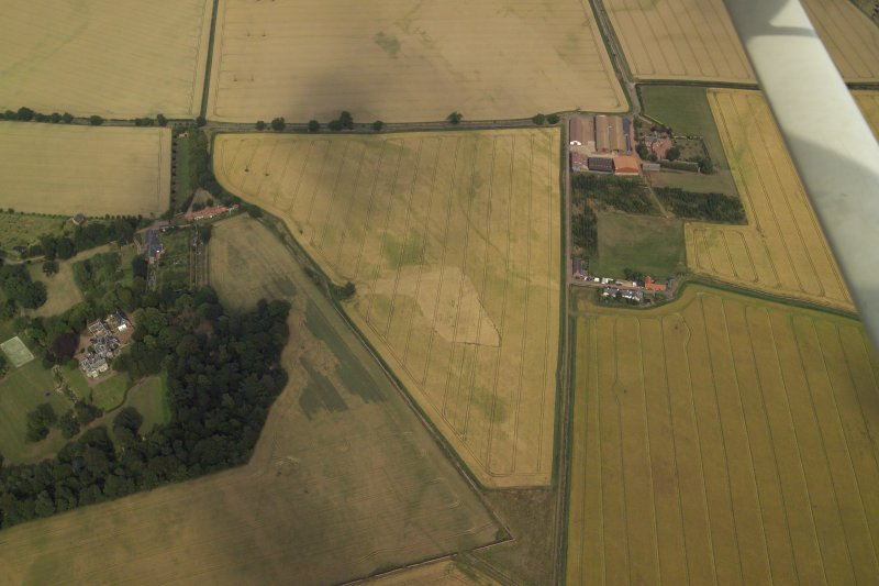 Oblique aerial view centred on the cropmarks of the field boundary and the cropmarks of the quarry with the farmhouse, farmsteading, country house, walled garden and dovecot adjacent, taken from the WSW.